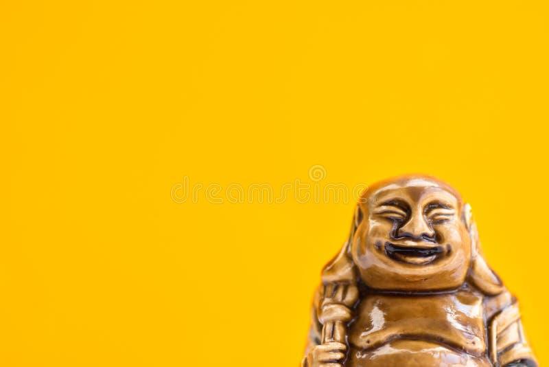 笑明亮的橙色背景的菩萨陶瓷雕象  佛教宗教标志 最低纲领派激动人心的图象 免版税图库摄影