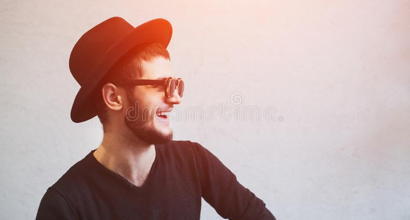 笑有胡子的人佩带的太阳镜和黑帽会议画象  免版税库存照片