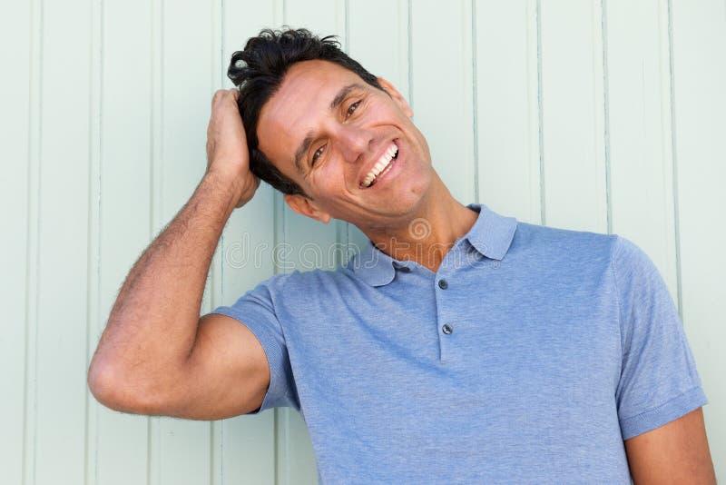 笑用在头发的手的愉快的中年人 库存图片