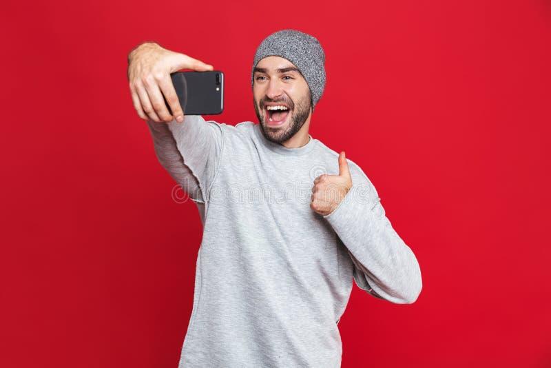 笑白种人人的图象,当拍在手机的selfie照片被隔绝在红色背景时 库存图片