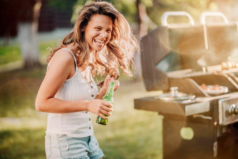 笑白肤金发的女孩画象有了不起的时光在烤肉格栅党 库存图片