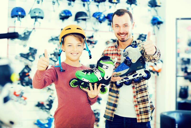 笑的人和儿子吹嘘的路辗冰鞋 免版税图库摄影