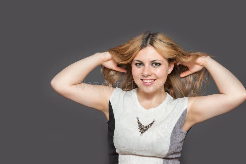 笑的俏丽的妇女投掷她长的棕色头发户内 图库摄影