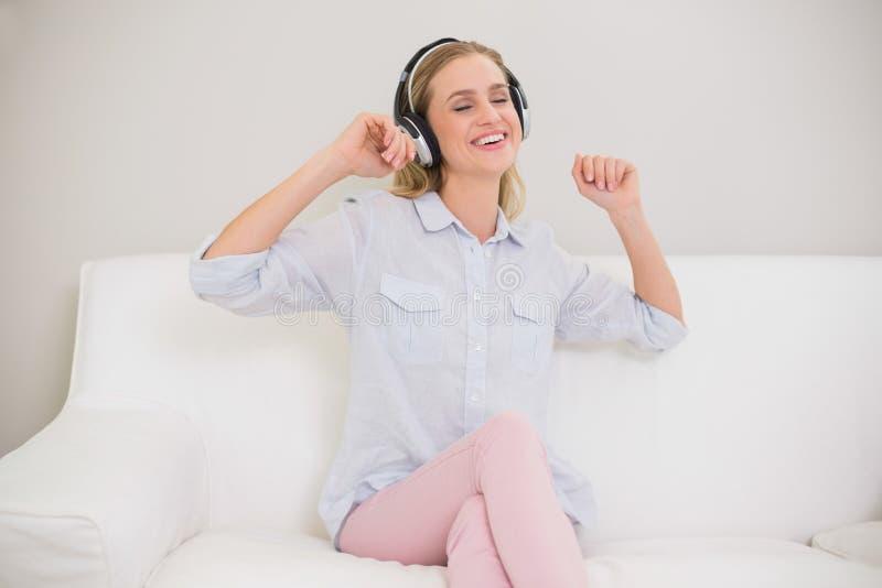 笑的偶然白肤金发听到音乐 库存照片