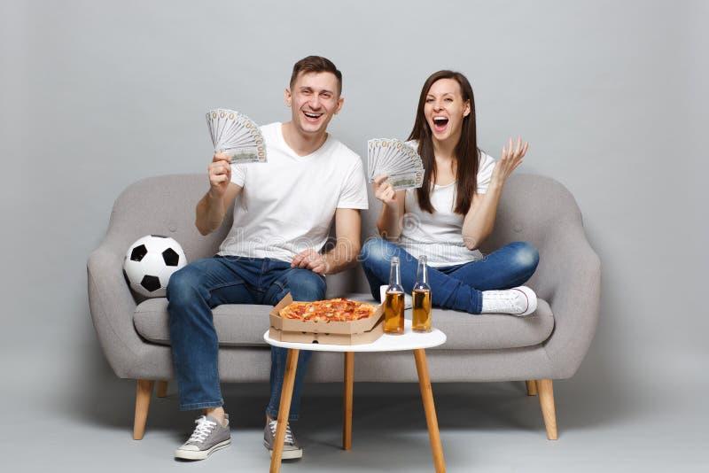笑的夫妇妇女人足球迷在美元钞票欢呼金钱,现金支持喜爱的队藏品爱好者  免版税库存图片
