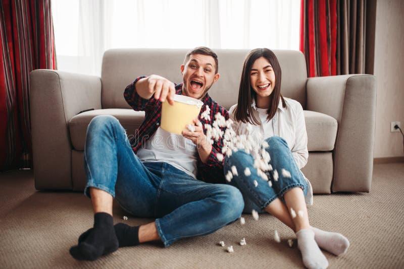 笑的夫妇手表喜剧电影用玉米花 图库摄影