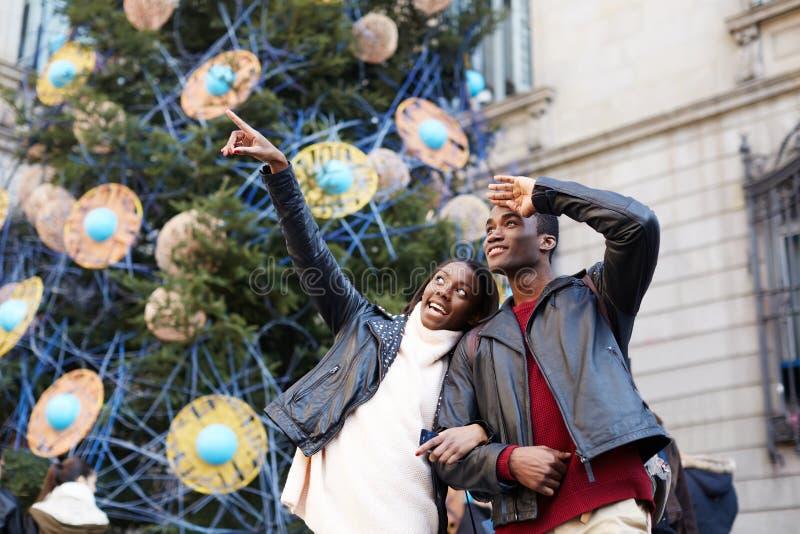 笑的夫妇走在城市的圣诞节假期 免版税库存照片