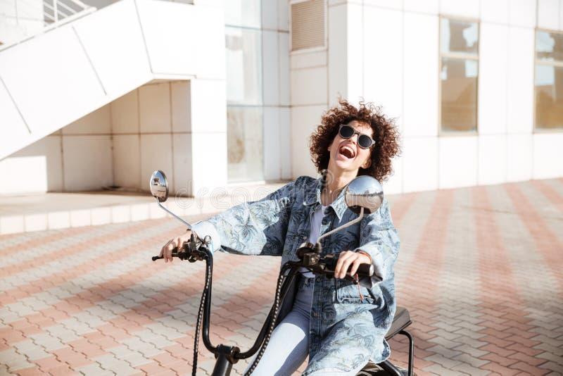 笑的女孩侧视图摆在摩托车的太阳镜的 免版税库存图片