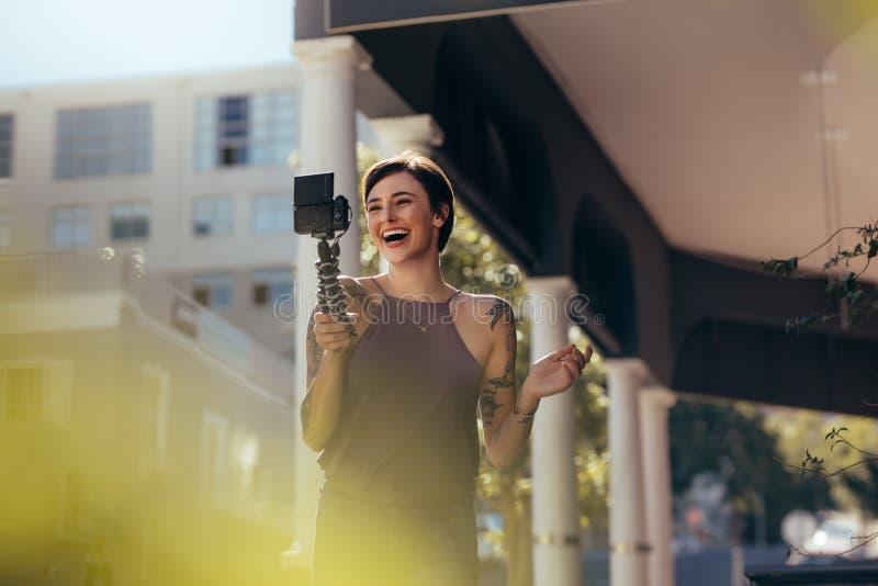 笑的妇女录音vlog户外 免版税库存照片