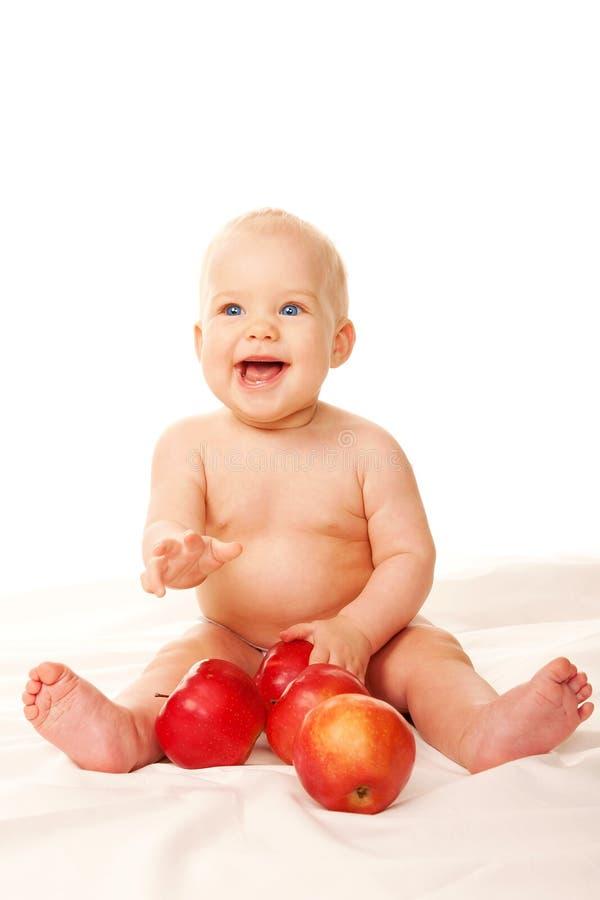 笑的婴孩用大红色苹果 库存图片