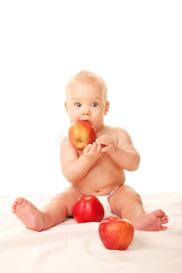 笑的婴孩用大红色苹果 免版税库存图片