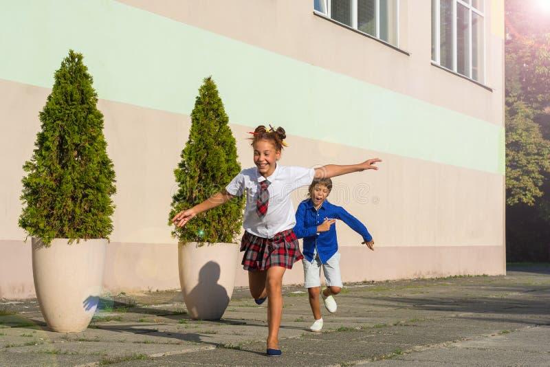 笑的学童-女孩和男孩在Th附近跑 图库摄影