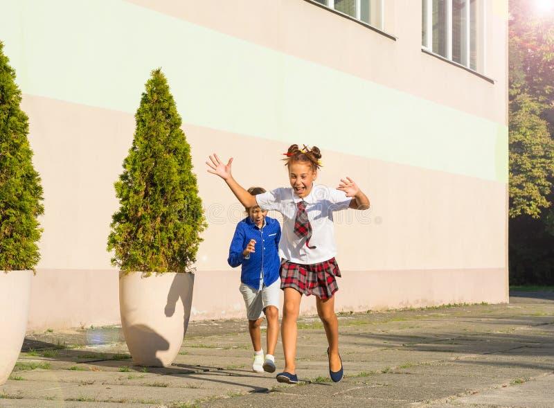 笑的学童-女孩和男孩在Th附近跑 免版税库存图片