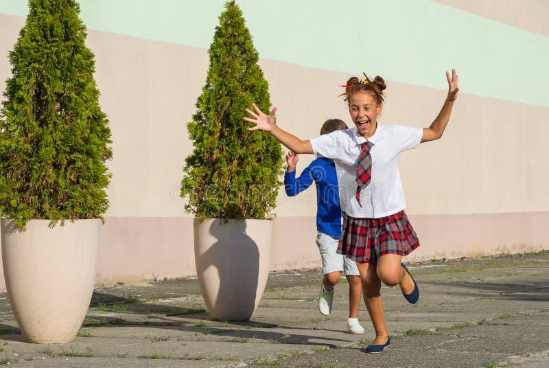 笑的学童-女孩和男孩愉快地跑a 图库摄影