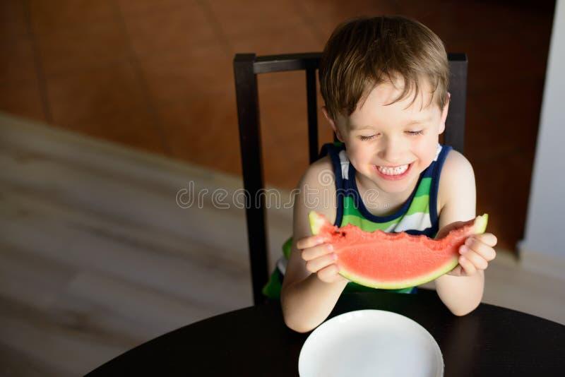 笑的学龄前儿童吃一个西瓜在桌上 免版税库存照片