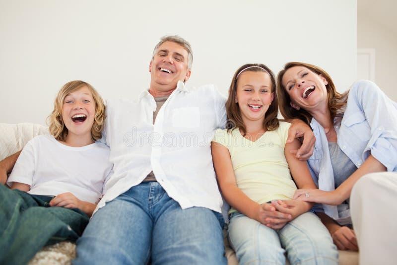 笑的家庭坐沙发 图库摄影