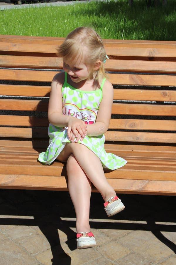 笑的小女孩,当坐长凳在城市公园时 正面儿童` s情感 免版税库存照片