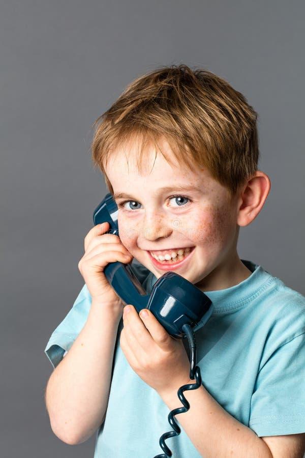 嘻嘻笑的小男孩谈话在一个蓝色古板的电话 库存图片