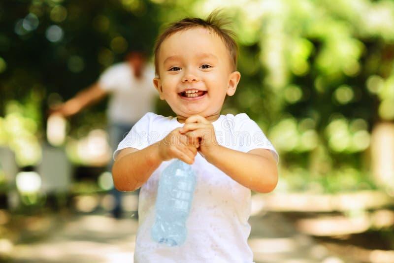 笑的小男孩跑室外与一个瓶清楚的饮用水,他的父亲在背景中被弄脏 重要性 库存图片