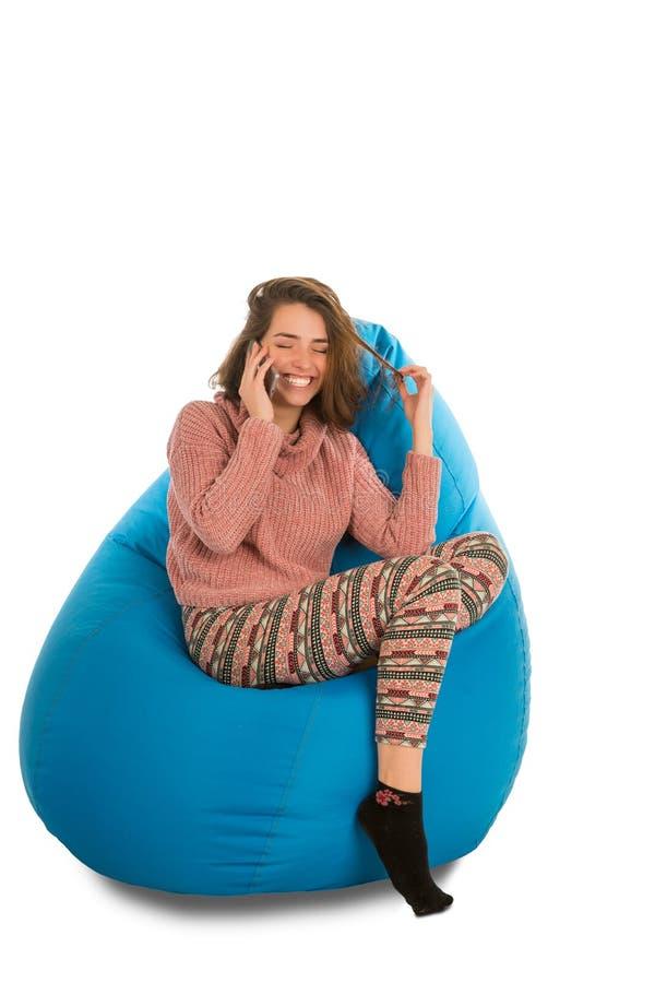 笑的少妇坐蓝色装豆子小布袋主持和谈的o 免版税库存照片