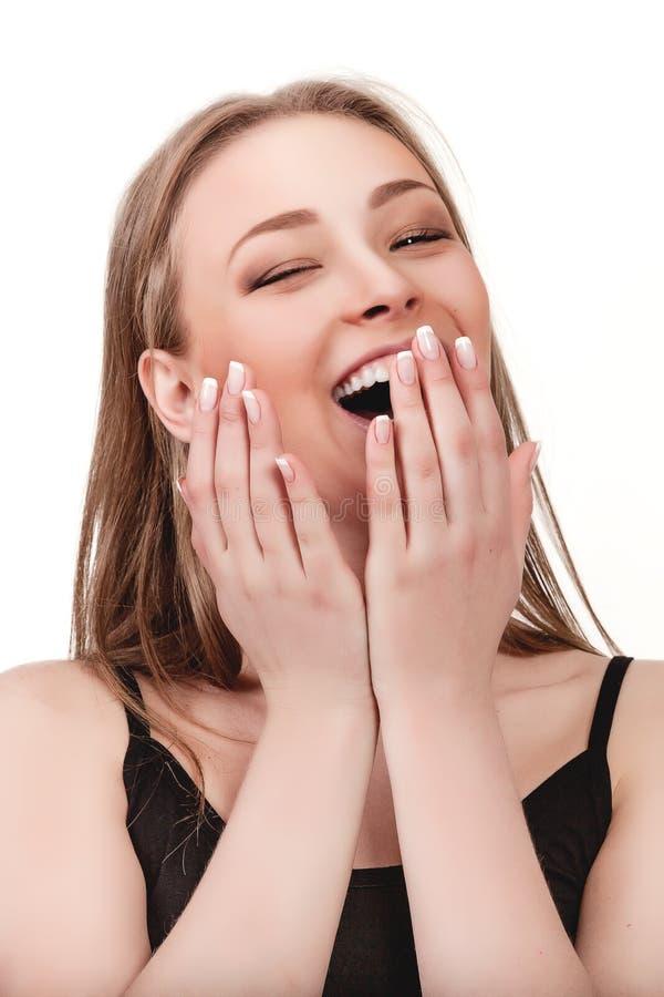 笑的少妇,在嘴的手 免版税库存图片