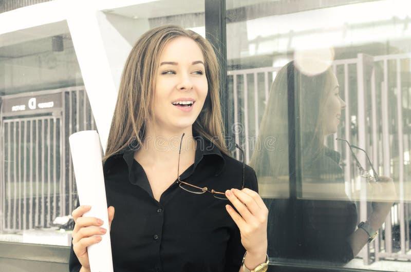 笑的少妇,当站立在一个大厦附近,与纸和玻璃在手上时 免版税库存照片