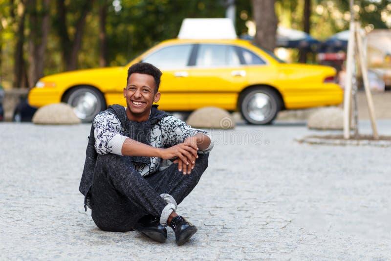 笑的年轻人摆在供以座位下来与在路的盘的腿,隔绝在黄色被弄脏的出租汽车背景 免版税库存图片