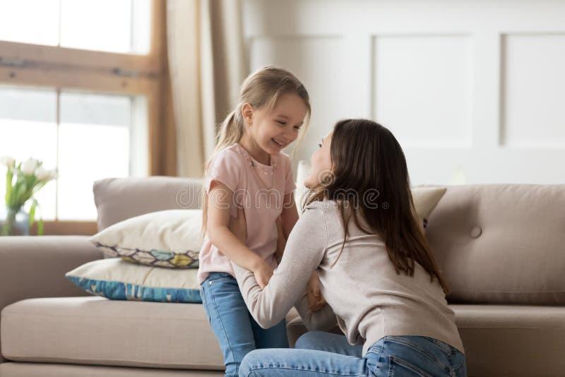 笑的母亲和的女儿看彼此感到愉快 免版税库存照片