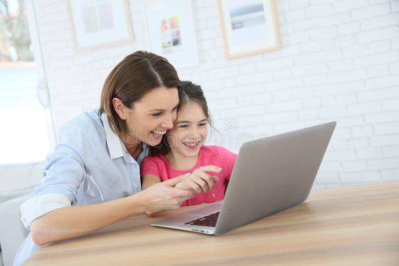 笑的母亲和的女儿,当打在膝上型计算机时的比赛 免版税库存图片