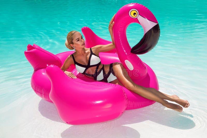 笑的游泳场的美丽的性感,惊人的年轻女人坐一可膨胀桃红色火焰状和,被晒黑的身体,长发 免版税库存图片