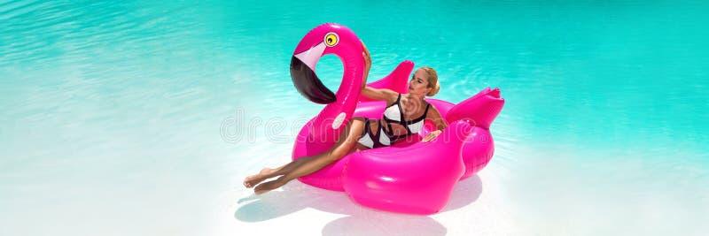 笑的游泳场的美丽的性感,惊人的年轻女人坐一可膨胀桃红色火焰状和,被晒黑的身体,长发 免版税库存照片