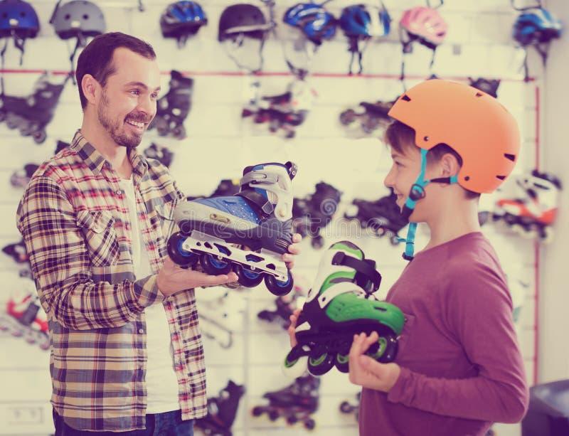 笑的父亲和男孩吹嘘的路辗冰鞋 免版税库存图片