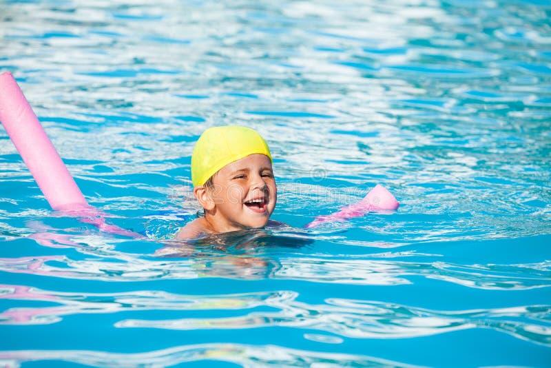 笑的男孩学会如何游泳用水池面条 库存照片