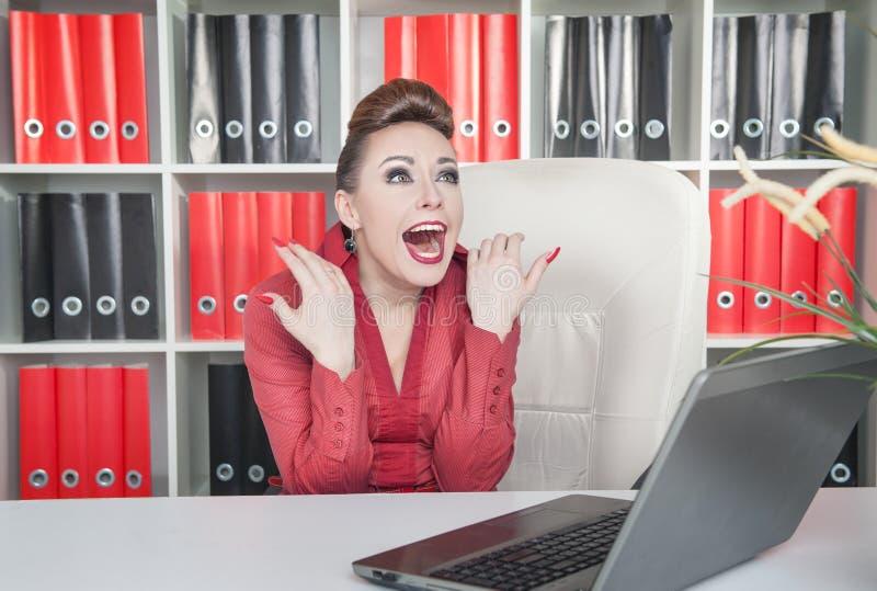 笑的疯狂的女商人在办公室 库存图片