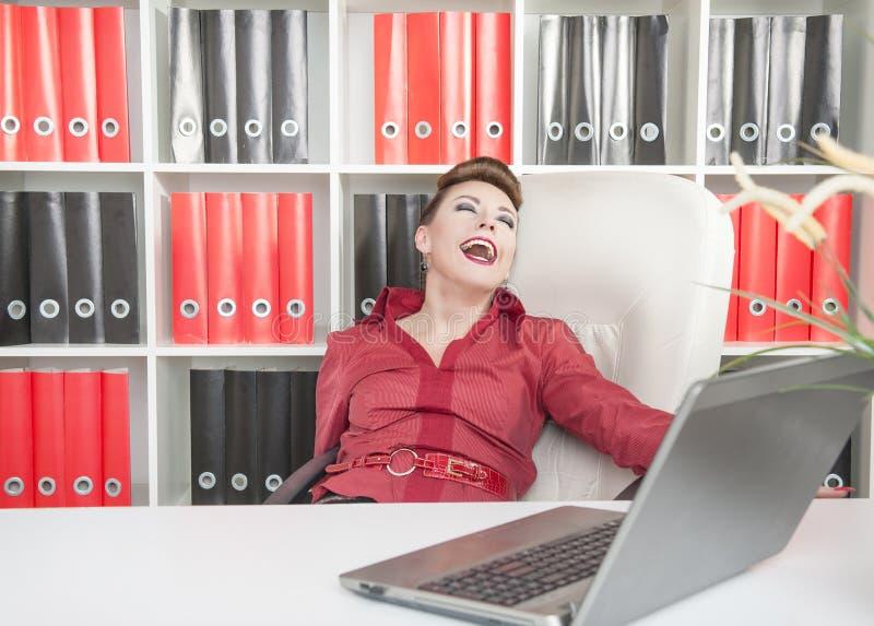 笑的疯狂的女商人在办公室 免版税库存图片