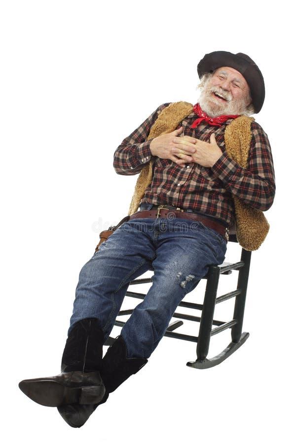 笑的老牛仔在摇椅倾斜  库存图片