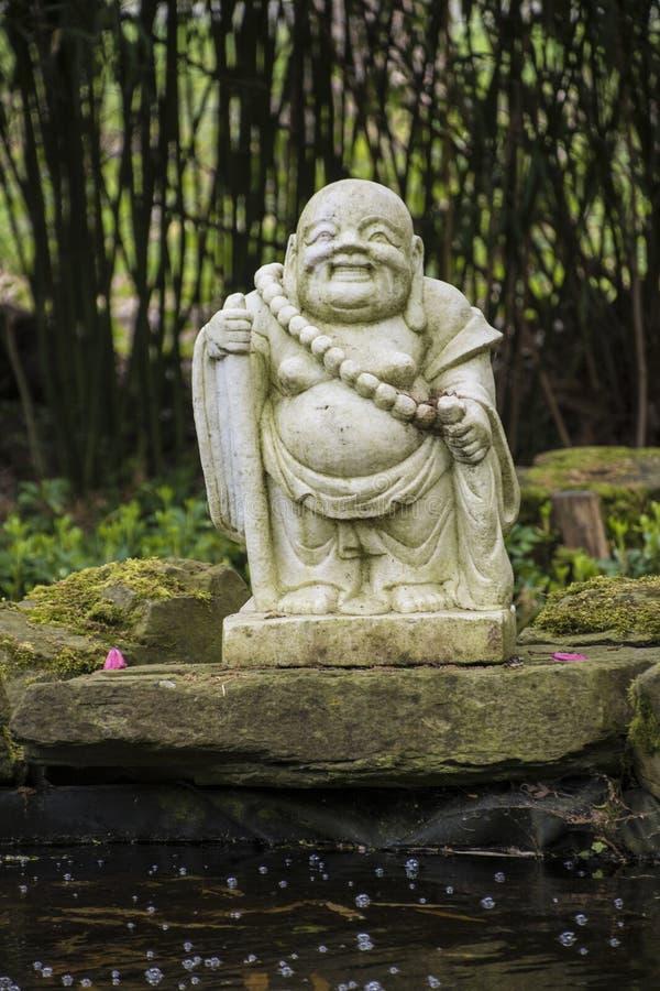 笑的老菩萨雕象-和平和和谐的标志 库存图片