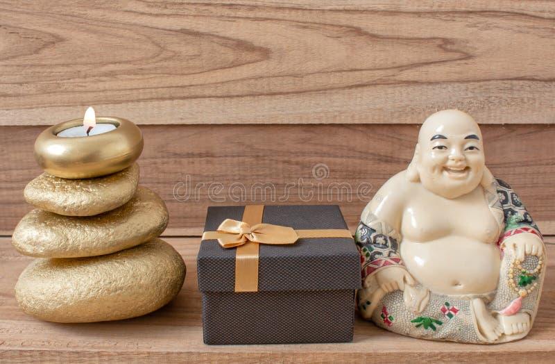 笑的菩萨的小雕象有石头和一个蜡烛的和一个礼物盒,在木背景,风水 免版税库存图片