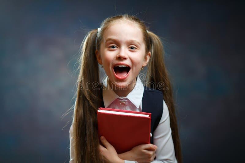 笑的长发女小学生举行红色书呼喊 库存图片
