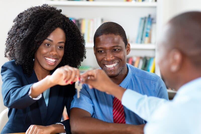 笑的非裔美国人的夫妇得到新的家的钥匙 免版税图库摄影