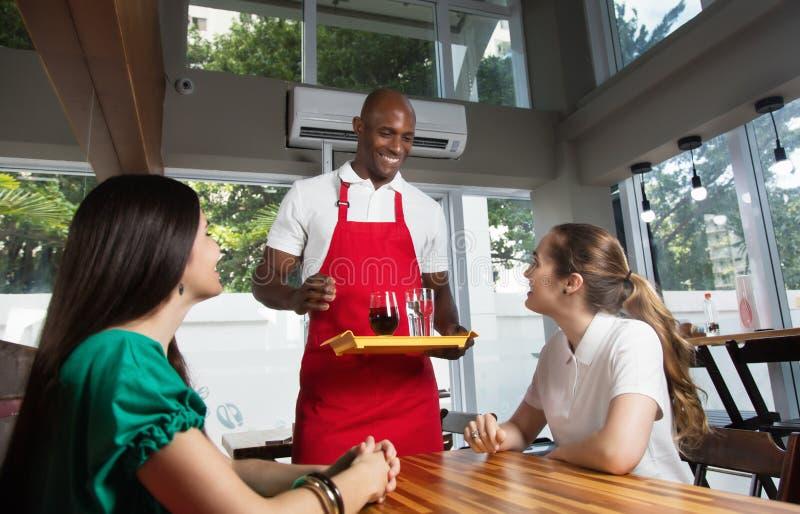 笑的非裔美国人的服务饮料 免版税库存照片
