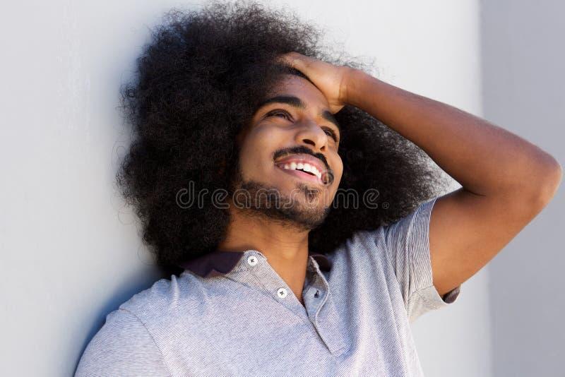 笑的非洲的人用在看的头发的手  免版税库存照片