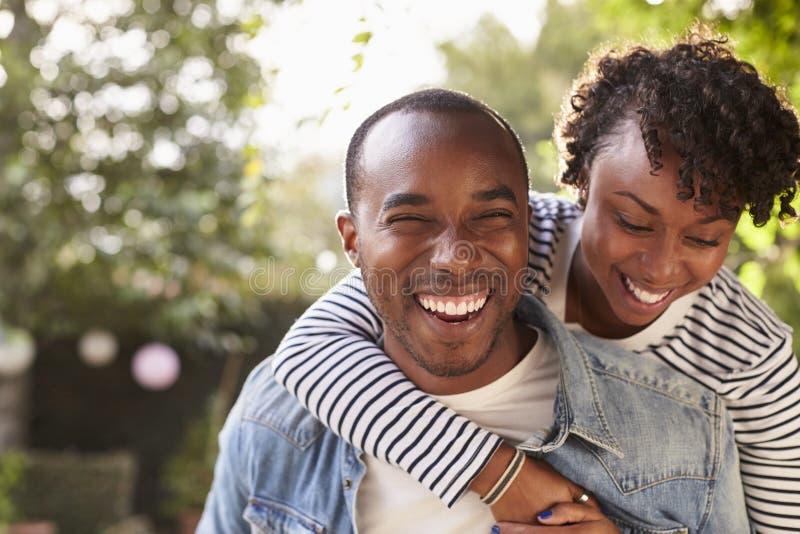 笑的年轻黑夫妇肩扛在庭院里,照相机的 免版税库存图片