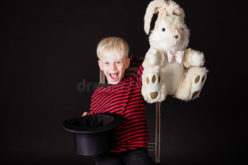 笑的活泼的小男孩魔术师 免版税库存照片