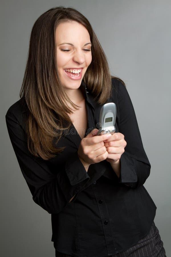 笑的texting的妇女 免版税库存图片