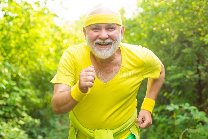 笑着快乐的老人跑步 正在运行 年龄不是放松身体的借口 老人练习运动 图库摄影