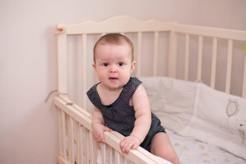 笑着的婴儿看着相机,在床上 免版税图库摄影