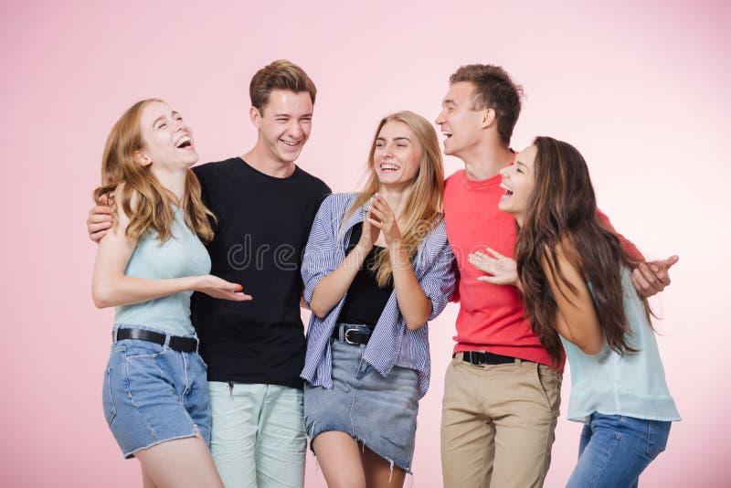 笑站立愉快的微笑的年轻的小组的朋友一起谈话和 最好的朋友 免版税库存图片