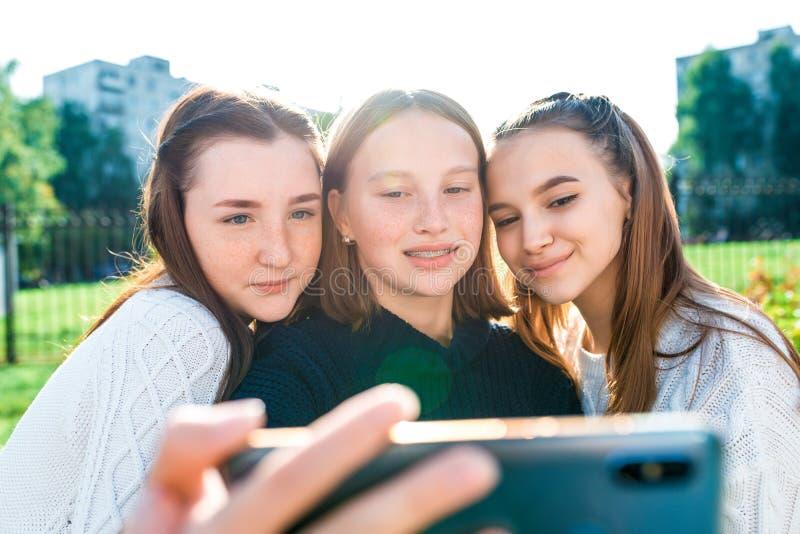 笑笑笑的三个女学生在智能手机上拍照 在电话、社交网络、网上自拍 免版税库存图片