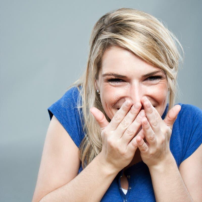 嘻嘻笑美丽的白肤金发的妇女 免版税图库摄影